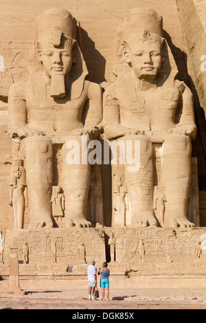 Two tourists in front of the Great Temple at Abi Simbel. - Stock Photo