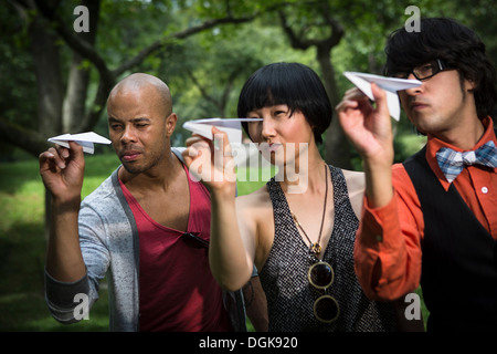 Three friends throwing paper planes in park - Stock Photo