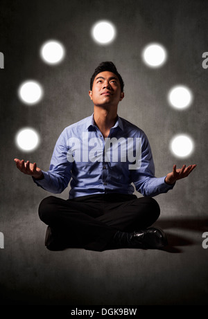 Businessman juggling balls of light - Stock Photo