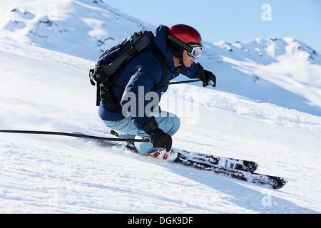 Male skier speeding down mountain - Stock Photo