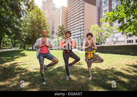 Three young people doing yoga in park - Stock Photo