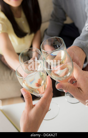 Mature friends toasting with white wine - Stock Photo