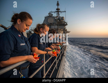 Sailors aboard the guided-missile cruiser USS San Jacinto (CG 56) pray for suicide victims during a suicide prevention - Stock Photo