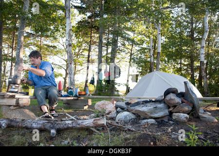 Mature man cooking on campsite, Bath, Maine, USA - Stock Photo