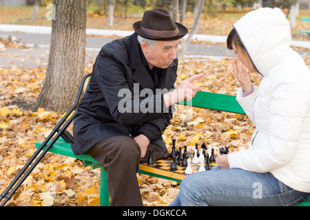 Elderly man arguing during a game of chess shaking a finger at a younger woman as the two sit together on a wooden - Stock Photo