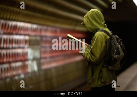 Prague metro station Staromestska, man reading a book, Prague, Czech Republic - Stock Photo