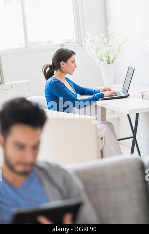 Woman using laptop and man using digital tablet at home - Stock Photo