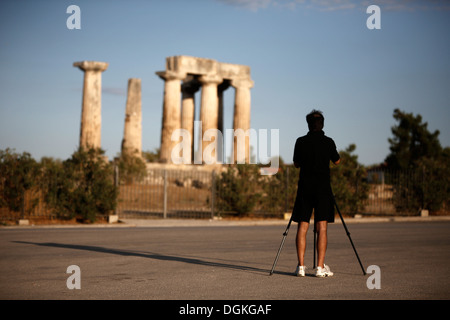 Tourist photographing the Temple of Apollo in ancient Corinth, Greece. - Stock Photo