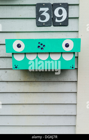 A custom made mailbox painted turquoise with eyes and teeth on the front of a house in St. John's, Newfoundland, - Stock Photo