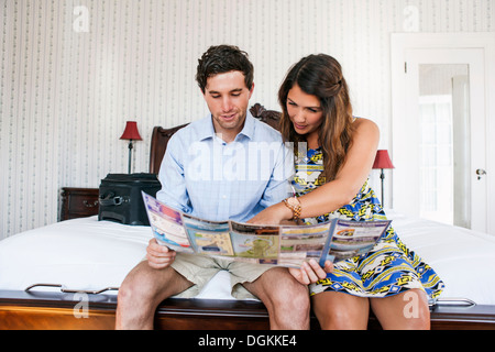 Young couple sitting on bed in hotel room and reading brochure - Stock Photo