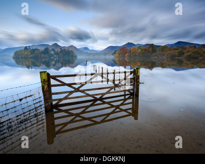A gate and fence in a flooded field by Derwent Water near Keswick. - Stock Photo