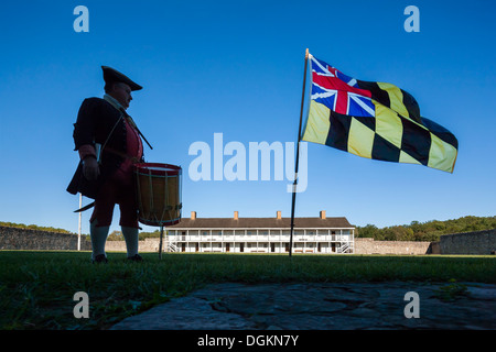 Historic daily life in Fort Frederick Maryland volunteer drummer with colonial era Maryland flag and East barracks. - Stock Photo