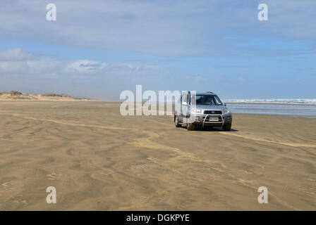 Car driving at low tide on Ninety Mile Beach, Hukatere, North Island, New Zealand - Stock Photo
