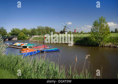 Siel canal with rental boats in front of the twin windmills of Greetsiel, Krummhoern, East Frisia, Germany, Europa - Stock Photo