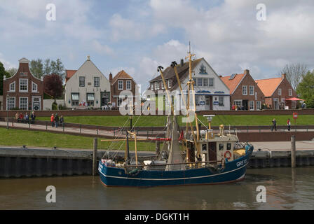 Shrimp boats in Greetsiel Harbour in front of the old dike, Krummhoern, East Frisia, Lower Saxony - Stock Photo