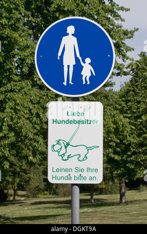 Sign in a park: foot path, Liebe Hundebesitzer, Leinen Sie Ihre Hunde bitte an or dog owners, please keep your dog - Stock Photo