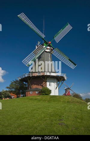 Twin windmills of Greetsiel, Dutch gallery windmill, western windmill at front, tea rooms, Krummhoern, landmark - Stock Photo