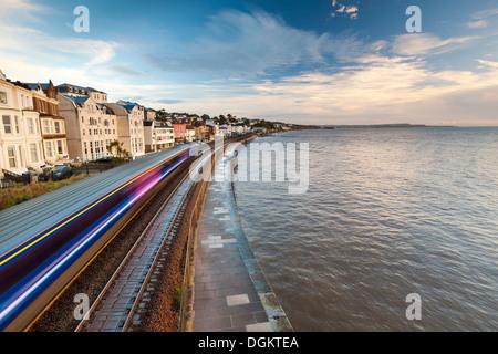 Great Western train passing through Dawlish on the famous Brunel southern coastal railway line. - Stock Photo