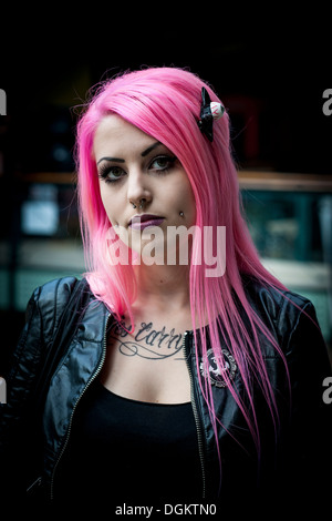 Atrractive girl with pink hair and face piercings at the London International Tattoo Convention. - Stock Photo