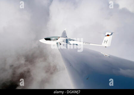 Glider type ASH 26 E above the clouds, Ratzeburg, Schleswig-Holstein, Germany - Stock Photo