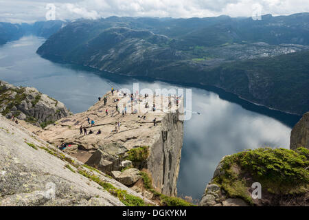 Preikestolen or Prekestolen, Preacher's Pulpit or Pulpit Rock with tourists, views across the fjord landscape, Preikestolen - Stock Photo