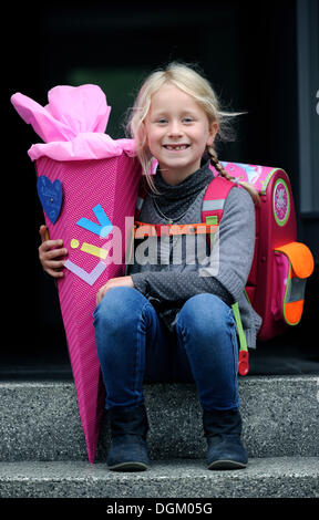 Girl, 6 years, with school backpack and school cone with treats for the first day of school - Stock Photo