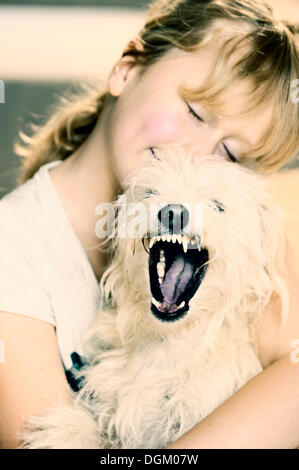 Girl, 9, cuddling with a young mixed-breed dog - Stock Photo