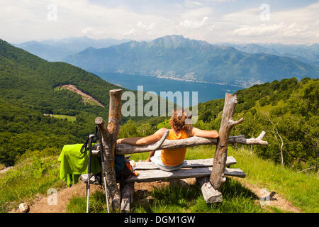Woman taking a break on a wooden bench while hiking on Monte Gambarogno on lake Lago Maggiore, Ticino, Switzerland, - Stock Photo