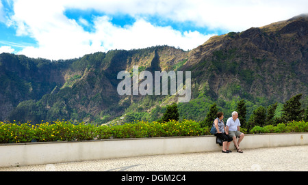 Curral das Freiras Madeira. Tourists sitting on a wall with mountain scenery behind also known as Nuns valley - Stock Photo
