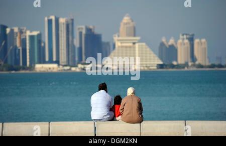 Family on corniche, promenade, Sheraton Hotel, skyline of Doha, Qatar, Persian Gulf, Middle East, Asia - Stock Photo