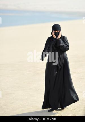 Arab woman in traditional clothing with abayah and veil, Khor Al Udeid Beach, Khor El Deid, Inland Sea, desert miracle - Stock Photo
