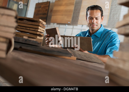 A young man in a workshop. Examining a reclaimed wood sample. - Stock Photo