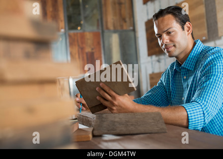 A young man in a workshop examining a recycled wood sample. - Stock Photo