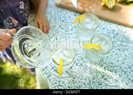 Making lemonade Overhead shot of lemonade glasses fresh slice of lemon in edge of glass child pouring drink from - Stock Photo