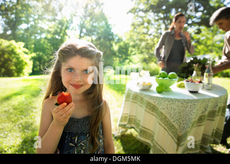 A young girl holding a large fresh organically produced strawberry fruit. Two adults beside a round table. - Stock Photo