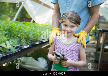 On farm Children adults working together man young child gardening gloves standing beside bench of young seedling - Stock Photo