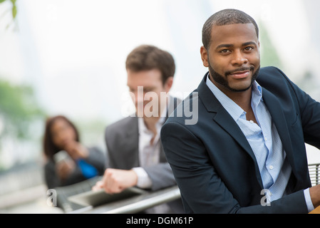 Summer. Three people sitting outside working. Using a digital tablet and smart phones. - Stock Photo