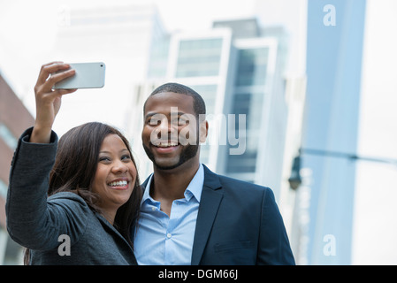 Summer. A couple taking a selfy, a woman holding out a smart phone and taking their picture. - Stock Photo