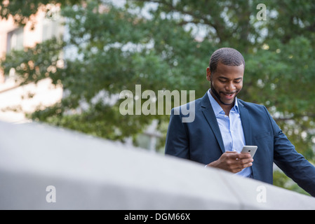 Summer. A man in a blue jacket and open collared shirt using a smart phone. - Stock Photo