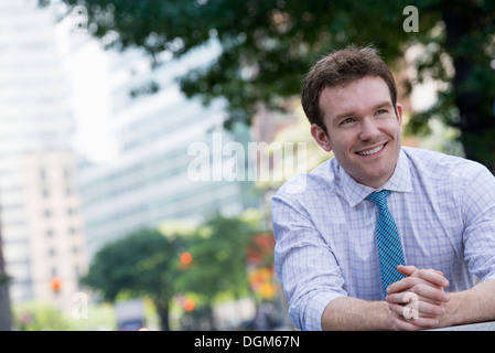 Summer. A man in a white shirt and blue tie with his hands clasped, leaning on a railing. - Stock Photo