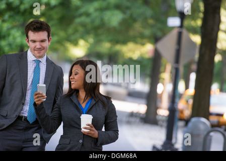 Summer. A young man in a grey suit and blue tie walking with a woman in a suit. White man, black african american - Stock Photo