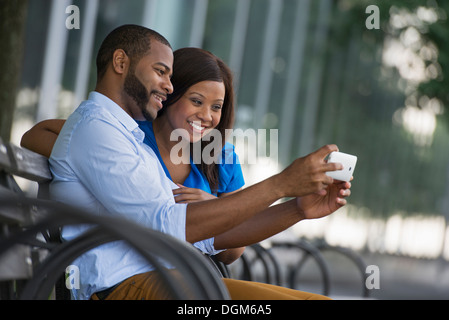 Summer. A couple sitting on a bench, taking a selfy photograph. - Stock Photo
