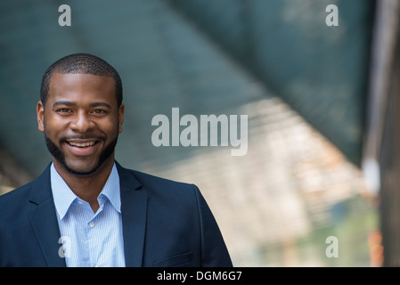 Summer. A man in a blue jacket and open necked shirt. Smiling. - Stock Photo