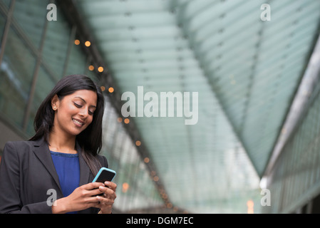 Business people. A young woman in a blue dress and grey jacket. - Stock Photo