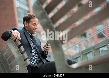Business people. A man in a suit, sitting on a bench. - Stock Photo