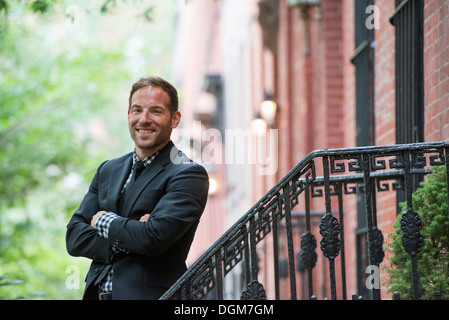 Business people. A man in a suit on the steps of a brownstone building. Arms folded. - Stock Photo