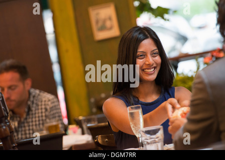 Business people. Two people seated at a table holding hands. A man in the background. - Stock Photo