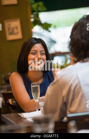 Business people. A couple seated at a table smiling at each other. - Stock Photo