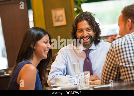 Business people. Three people seated around a table in a bar or cafe, having drinks. - Stock Photo