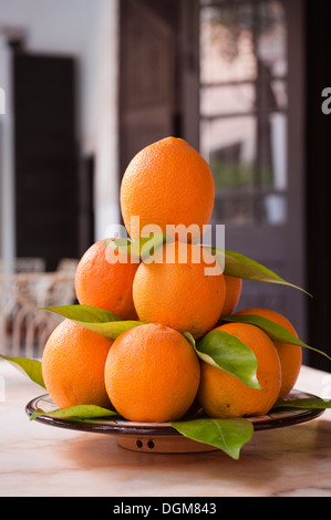 Pile of Moroccan oranges on ceramic dish - Stock Photo